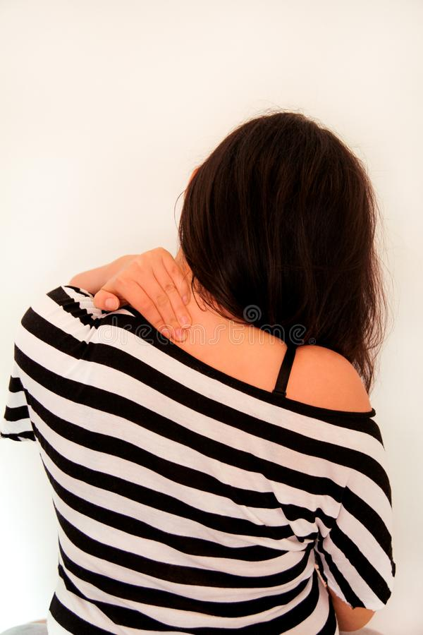 Tired handsome woman having pain in neck, rubbing it. Neck pain. Tired woman having pain in neck, rubbing it. Massage of the shoulder and neck. Pain in the neck royalty free stock images