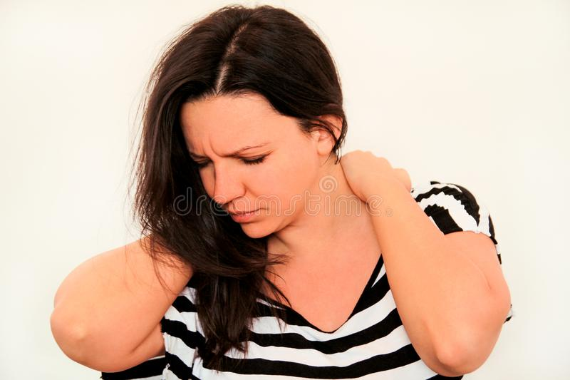 Tired handsome woman having pain in neck, rubbing it. Neck pain. Tired woman having pain in neck, rubbing it. Massage of the shoulder and neck. Pain in the neck royalty free stock photos