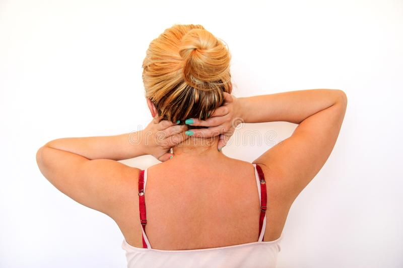 Tired handsome woman having pain in neck, rubbing it. Neck pain. Tired woman having pain in neck, rubbing it. Massage of the shoulder and neck. Pain in the neck stock photography