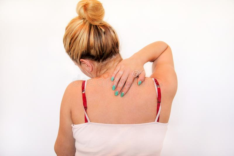 Tired handsome woman having pain in neck, rubbing it. Tired woman having pain in neck, rubbing it. Massage of the shoulder and neck. Pain in the neck and back royalty free stock photography