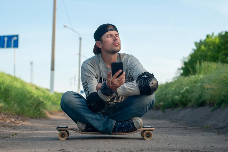 Tired happy young skater dozing sitting on a skateboard, breathing fresh air. People and the concept of relaxation,. Tired happy young skater dozing sitting on a royalty free stock image