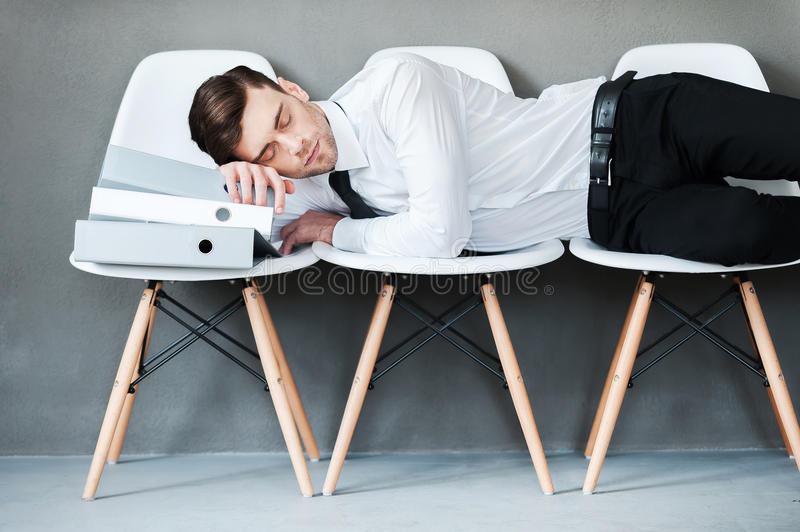 Tired after hard working. Tired young man keeping eyes closed while laying on chairs against grey background stock photo