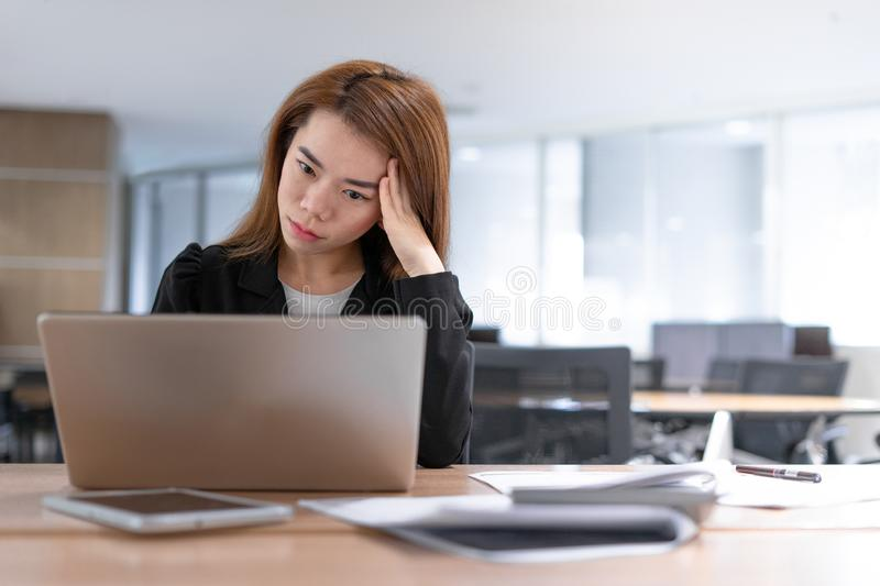 Tired and headache asian business woman closed eyes and sitting at desk looking at laptop in office background royalty free stock photos