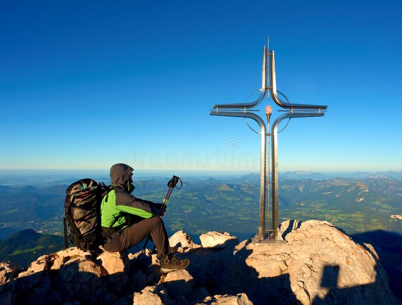 Tired hiker sit bellow crucifix on mountain peak. Iron cross at Alps mountain top. Relaxing tourist with poles and heavy backpack royalty free stock image