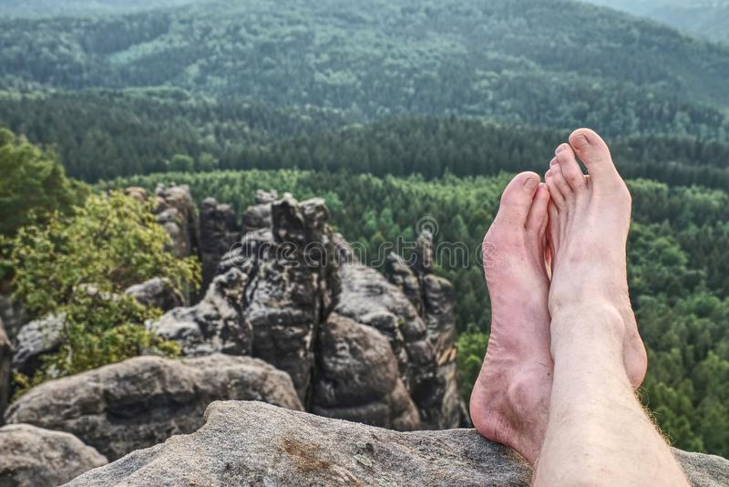 Tired hikers legs without shoes. Naked legs on peak. Tired hikers legs without shoes. Naked male hairy legs take a rest on peak of rock activity park part tree royalty free stock image