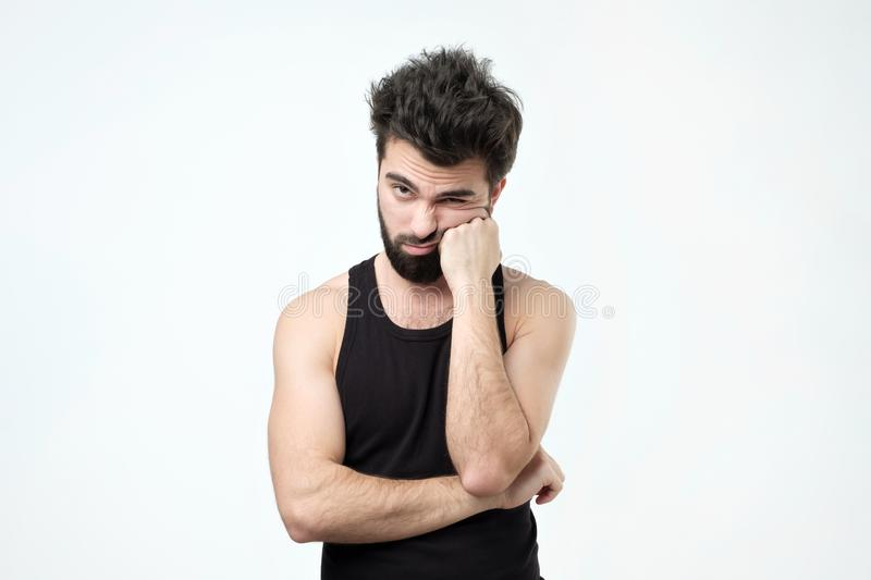 Tired hispanic guy with beard, being exhausted and wanting to get rest against gray background stock photography