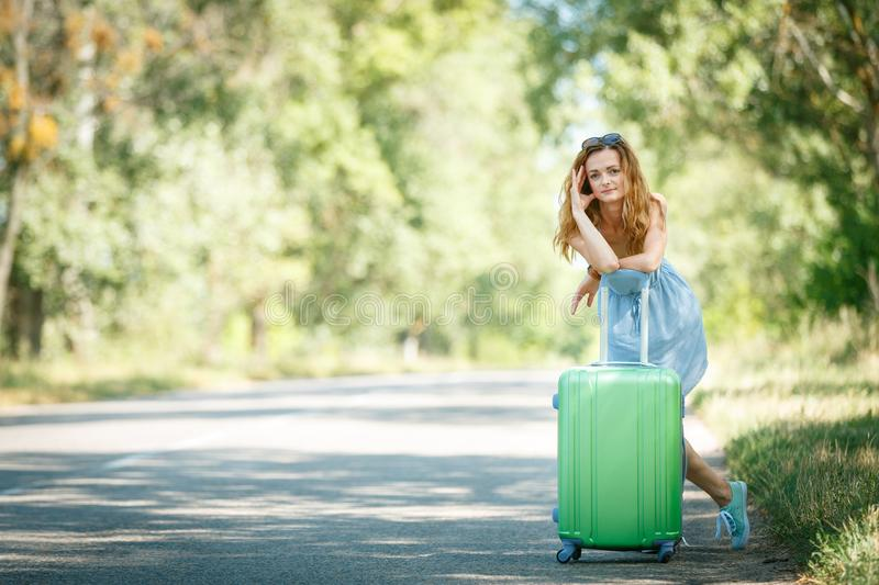 Hitchhiking girl looking for adventures. Tired Hitchhiking girl in a summer dress leaning on a case. Road adventure concept royalty free stock images