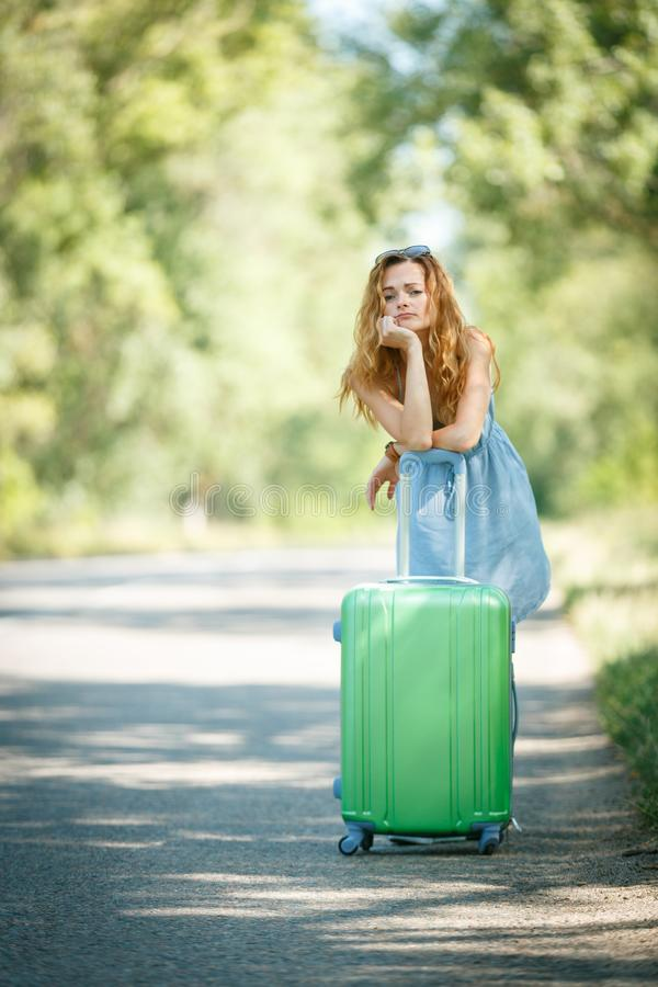 Hitchhiking girl looking for adventures. Tired Hitchhiking girl in a summer dress leaning on a case. Road adventure concept royalty free stock photo