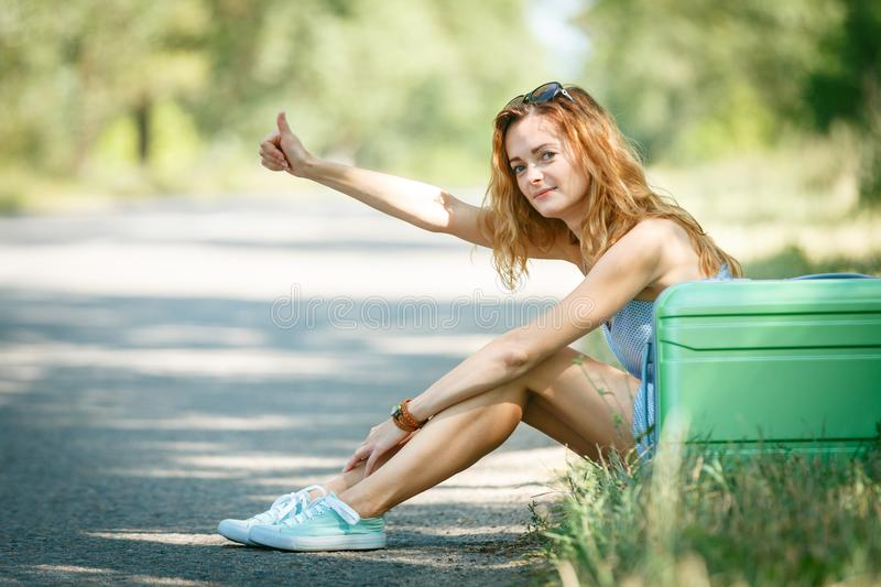 Tired Hitchhiking girl. In a summer dress sitting on a road with a green plastic case. Road adventure concept royalty free stock photos