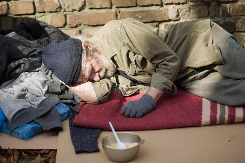 Tired homeless old man sleeping on cardboard in the street. royalty free stock images