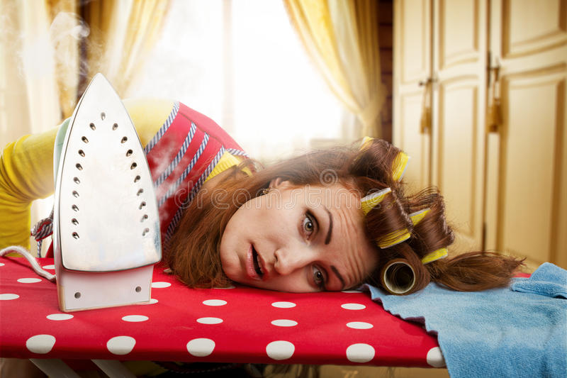 Tired housewife with ironing-board. Tired housewife lying on ironing-board royalty free stock photography