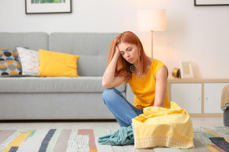 Tired housewife with laundry sitting on floor royalty free stock photos