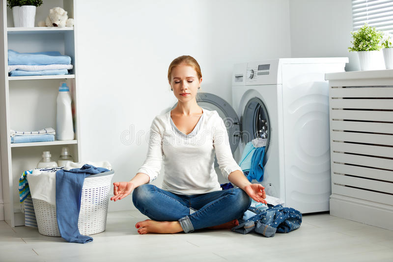Tired housewife meditates in lotus position in laundry room. Concept. tired housewife meditates in lotus position in laundry room near washing machine and dirty stock images