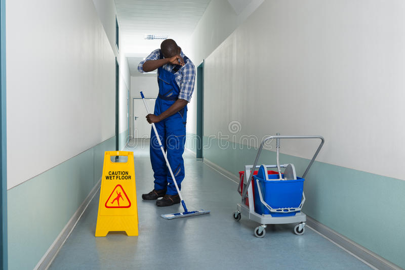 Tired Janitor Cleaning Floor stock photos