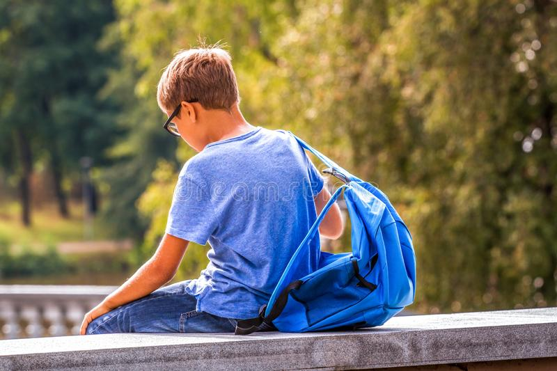 Tired kid with backpack sitting outdoors after school stock photography
