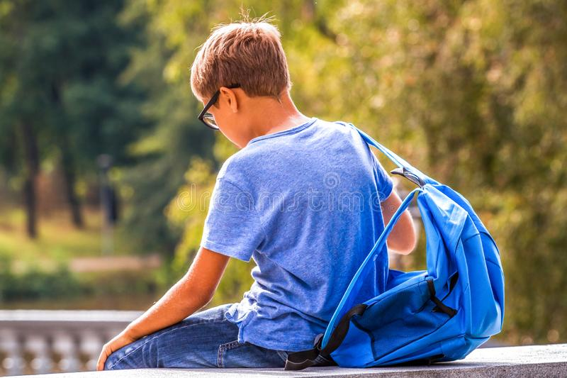 Tired kid with backpack sitting outdoors after school royalty free stock photography