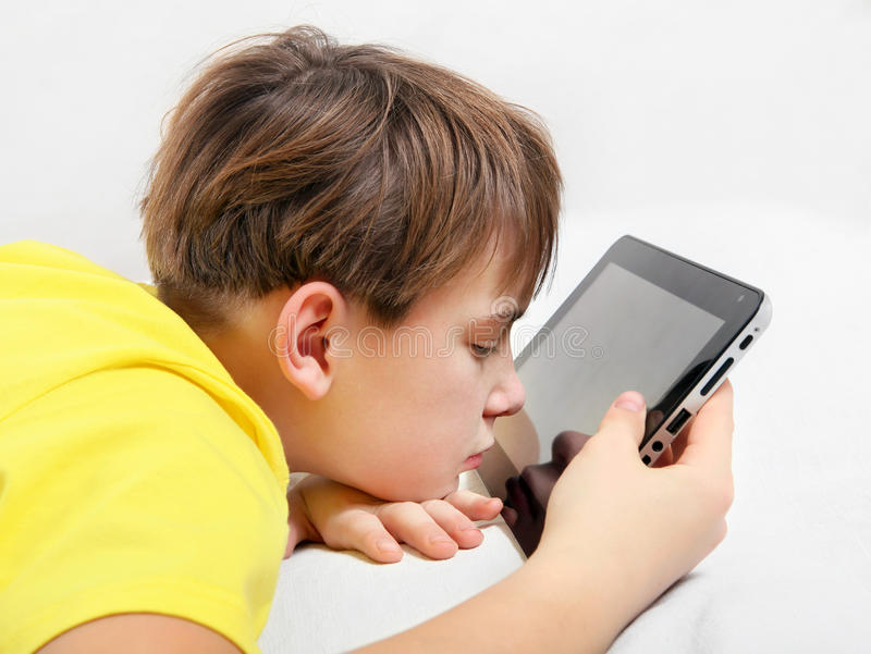 Tired Kid with Tablet Computer. On the Bed royalty free stock photography