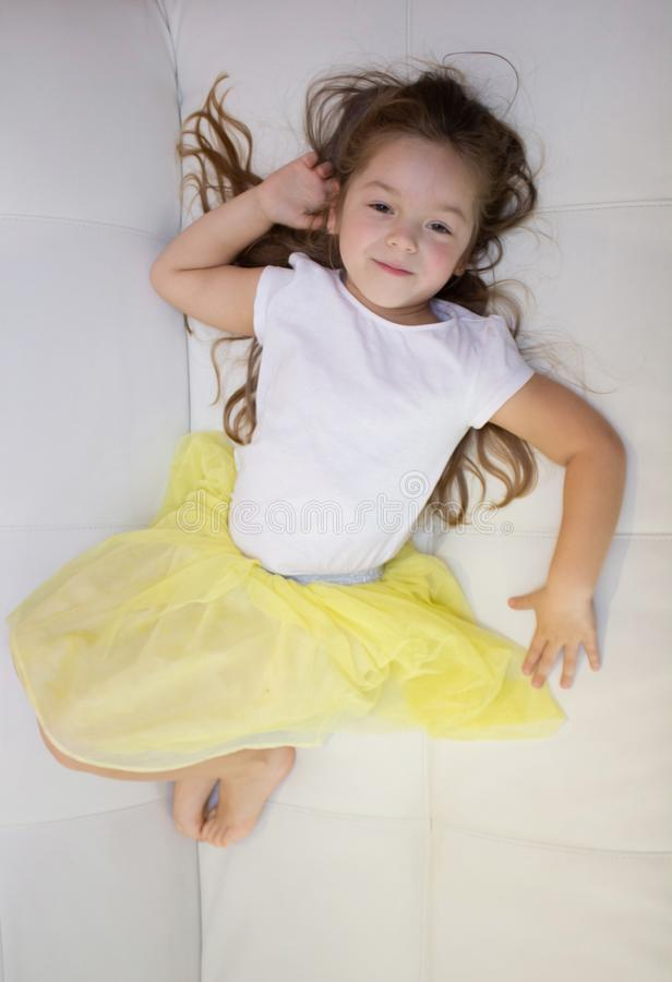 Tired lazy little girl lying on sofa at home. Sleepy kid resting relaxing on couch.  royalty free stock photo