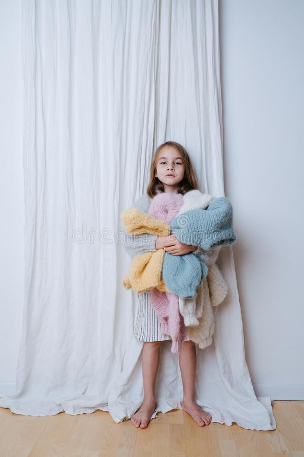 Tired little girl is holding pile of soft multi-colored freshly washed sweaters stock photos