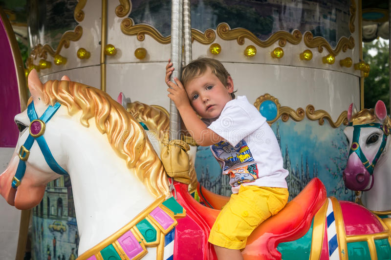 Tired little boy riding on roundabouts. In Gelendzhik in Russia on 23.06.2015 royalty free stock image