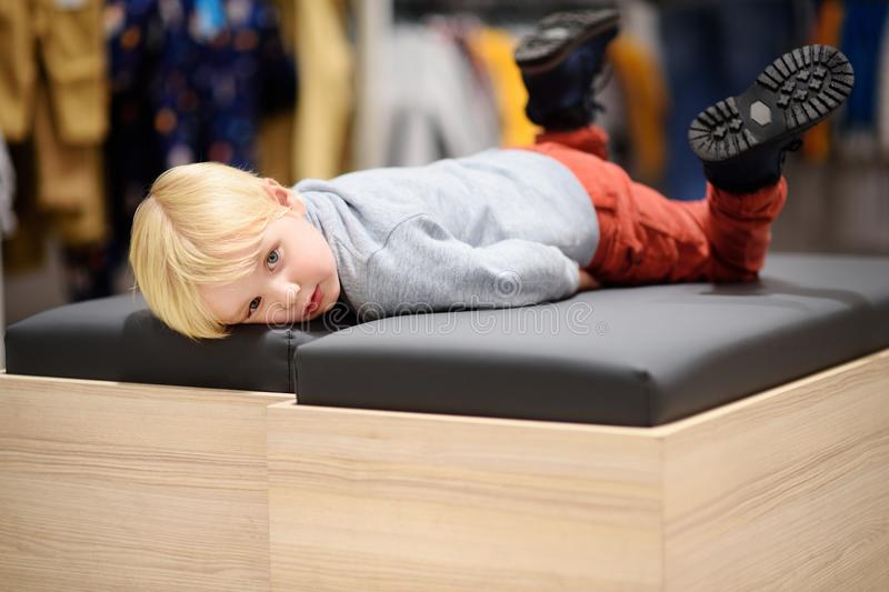 Tired little boy during shopping with parents. Fashion clothes for kids. Child in shopping center/mall or baby apparel store royalty free stock image
