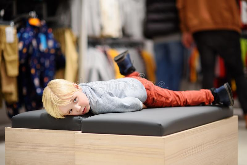 Tired little boy during shopping with parents. Fashion clothes for kids. Child in shopping center/mall or baby apparel store stock photo
