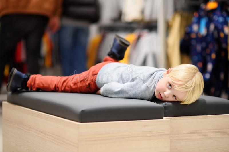 Tired little boy during shopping with parents. Fashion clothes for kids. Child in shopping center/mall or baby apparel store royalty free stock photo