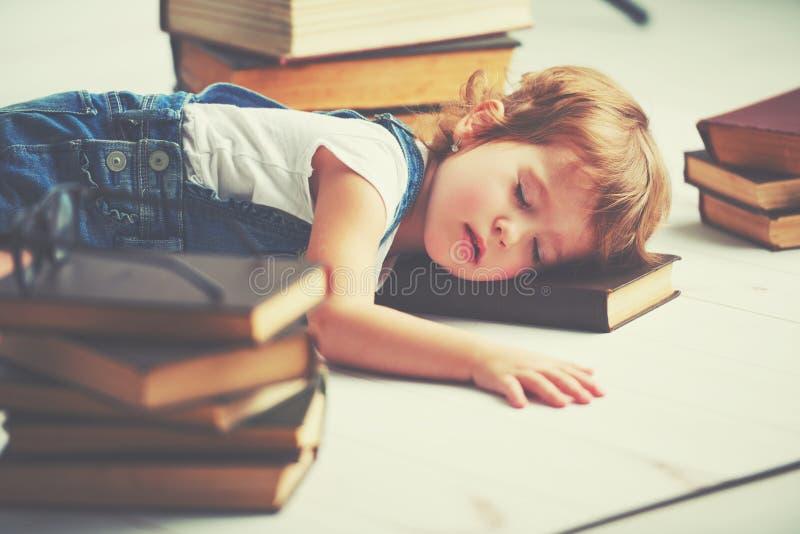 Tired little girl fell asleep for books stock photo