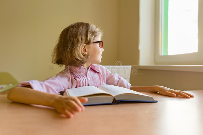 Tired little girl student looks out the window while sitting at her desk with a big book. School, education, knowledge and stock image