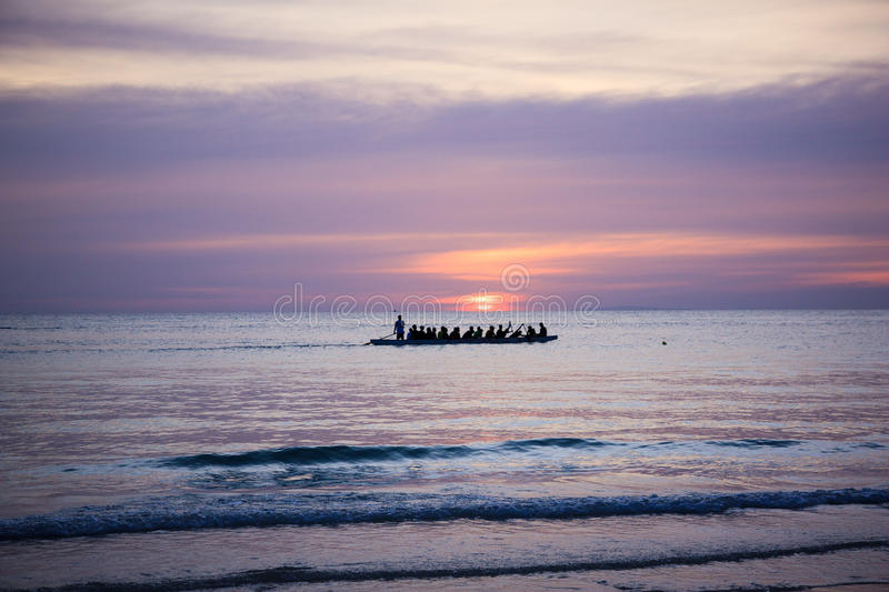 Tired locals go home after work. Work day is over and tired locals paddle a boat in Philippines, Boracay royalty free stock photos