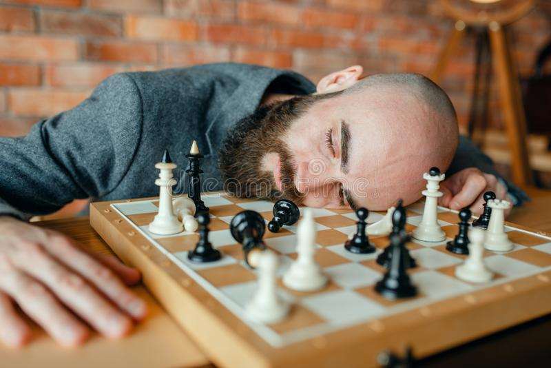 Tired male chess player sleeping on the board royalty free stock images
