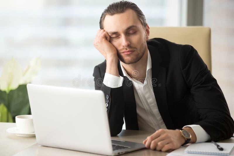 Tired male entrepreneur slumbers at work royalty free stock image
