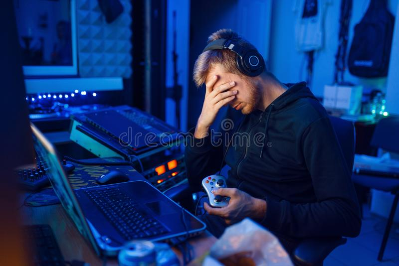 Tired gamer, gaming lifestyle, cyber addiction. Tired male gamer, gaming lifestyle, cyber addiction. Computer games dependence, videogame player in his room with stock photos