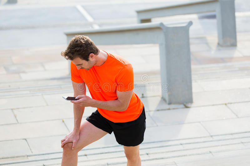 Tired male runner using cell telephone while resting after jog outside in summer day royalty free stock photos