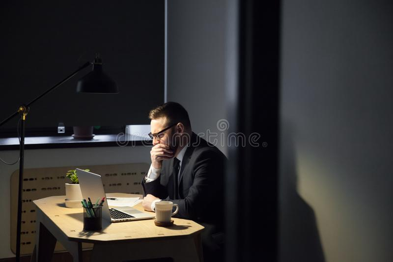 Tired male worker yawning spending late hours in office. Tired bored male office worker yawning and covering mouth being exhausted from working long hours royalty free stock images