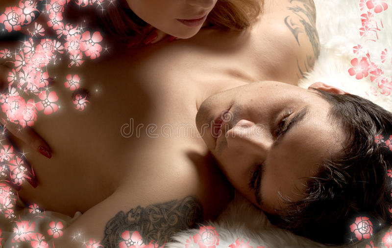 Tired man in bed with wife and flowers. Portrait of tired married men in bed with wife and flowers stock photography