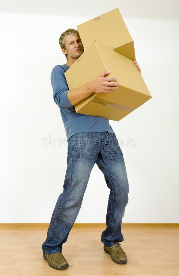 Tired man with cardboards. Tired young man holding cardboards. Looking at camera. Gray background, whole body royalty free stock photography