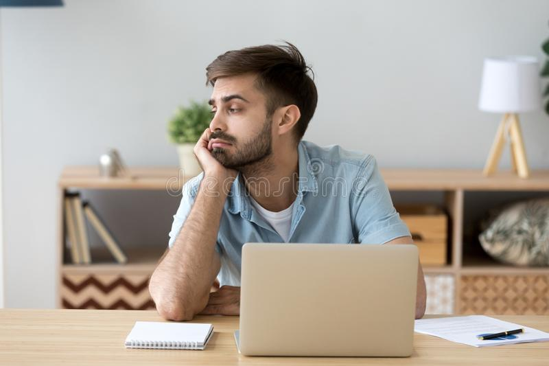 Tired man distracted from computer work lacking motivation. Tired male student or worker sit at home office desk look in distance having sleep deprivation, lazy stock photography