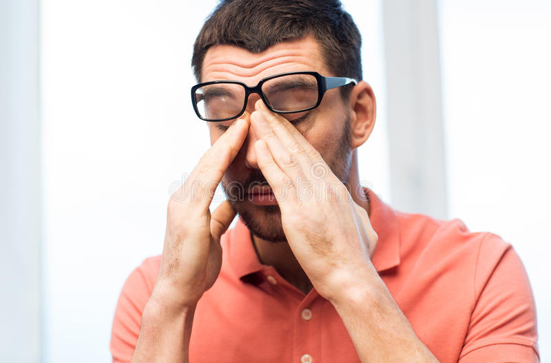 Tired man in eyeglasses rubbing eyes at home. People, eyesight, stress, overwork and business concept - tired man in eyeglasses rubbing his eyes at home or work stock image