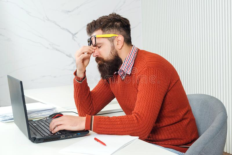 Tired man with laptop computer at working place. Bearded man overworked at office. Stressed handsome business man. Feeling royalty free stock photography
