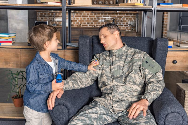 tired man in military uniform sleeping on armchair with son near stock image