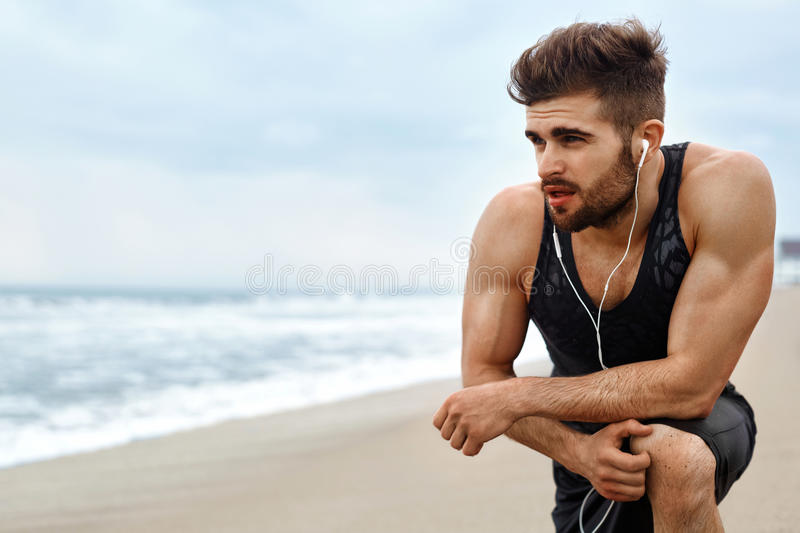 Tired Man Resting After Running On Beach. Sports Workout Outdoor stock image