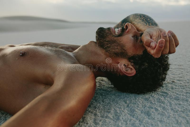 Tired man resting on sand after intense workout. Tired man relaxing after intense workout. Athlete taking rest on sand after a workout stock photography