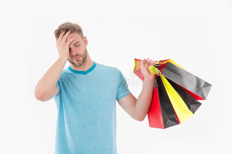 Tired man with shopping bags isolated on white. Macho with colorful paper bags. Fashion shopper in casual blue tshirt and shorts. Holidays preparation and royalty free stock photography