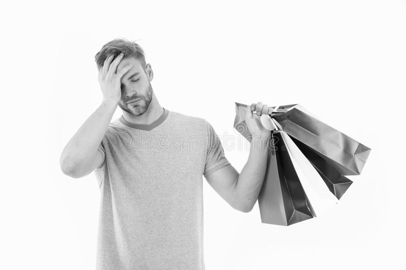 Tired man with shopping bags isolated on white. Macho with colorful paper bags. Fashion shopper in casual blue tshirt. And shorts. Holidays preparation and royalty free stock image