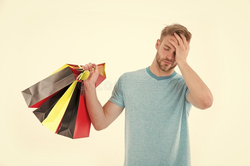 Tired man with shopping bags isolated on white. Macho with colorful paper bags. Fashion shopper in casual blue tshirt. And shorts. Holidays preparation and stock photos