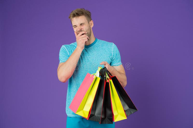 Tired man with shopping bags on violet background. Shopping or sale and cyber monday. Macho with colorful paper bags. Fashion shopper in casual blue tshirt stock photography