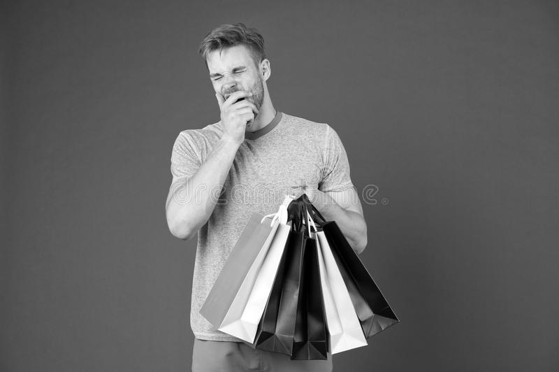 Tired man with shopping bags on violet background. Shopping or sale and cyber monday. Macho with colorful paper bags. Fashion shopper in casual blue tshirt stock image