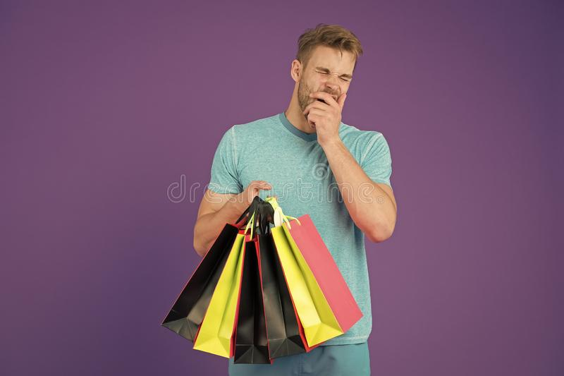 Tired man with shopping bags on violet background. Shopping or sale and cyber monday. Macho with colorful paper bags. Fashion shopper in casual blue tshirt stock photos