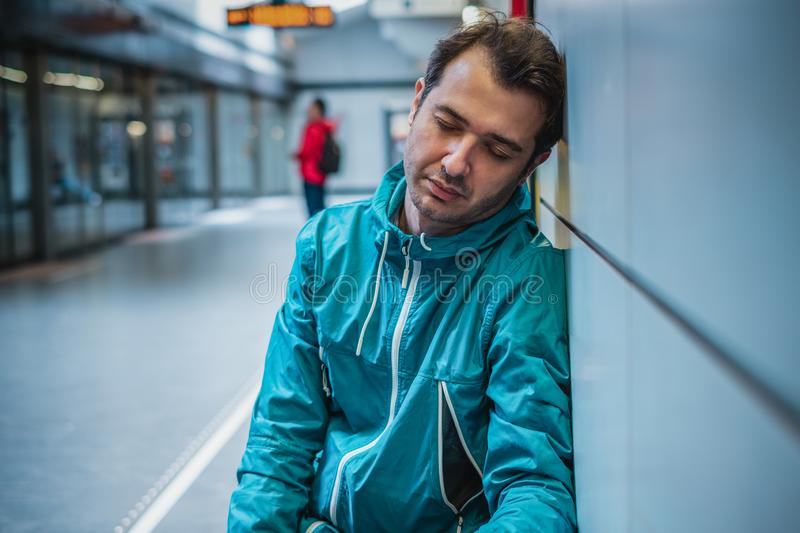 Tired man sleeps in the metro train station. One passenger sleeping at subway station royalty free stock photography